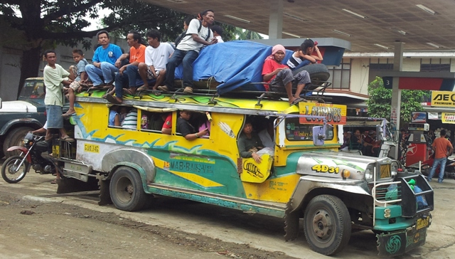An overloaded jeepney.  A common sight in the Philippines.